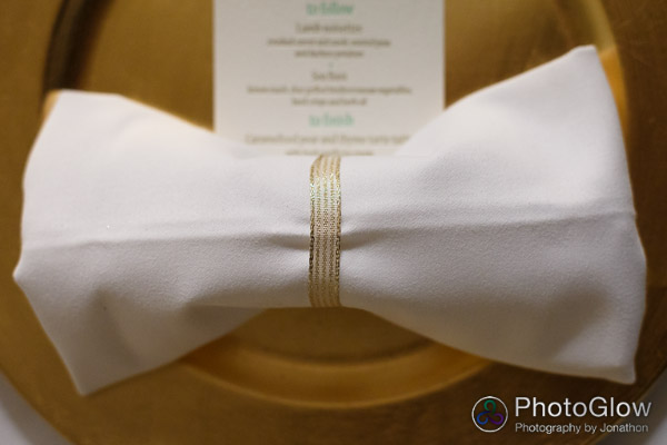 bow tie fold napkin with gold ribbon